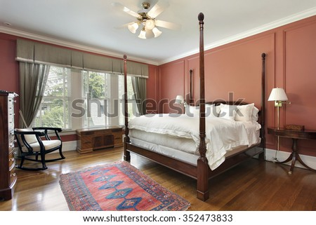 Master bedroom in luxury home with salmon colored walls - stock photo