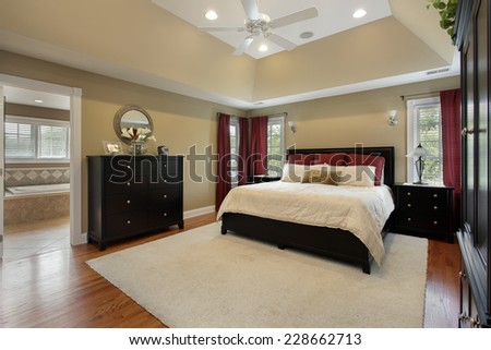 Master bedroom in luxury home with view into bathroom - stock photo