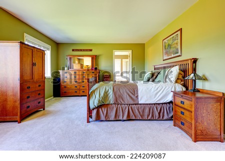 Master bedroom interior in bright green color with wooden bed, nightstand, bedroom vanity cabinet and wardrobe. - stock photo