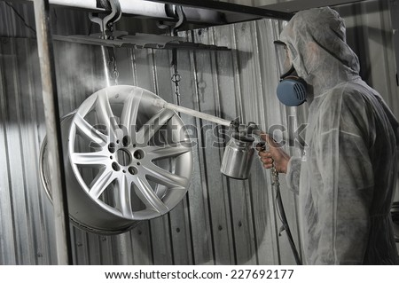 Master in protective suit paint paint sprayer car disc to the service station. Use powder coloring. - stock photo