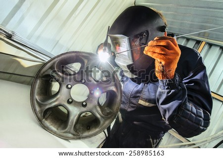 Master in the mask makes the weld rims - stock photo
