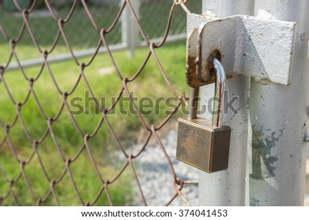 master key on old iron gate background. rustic lock, master key, padlock of outdoor gate. Rusty master key locked on the rusty door. - stock photo