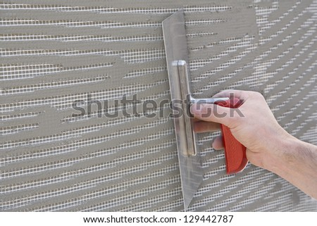 Master makes plaster on a wall with mesh and glue - stock photo