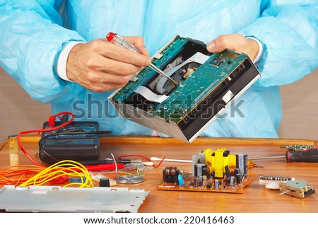 Master servicing electronic devices in the service workshop - stock photo