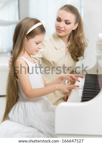 Master teaches little girl to play piano. Concept of music study and arts - stock photo