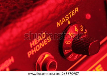 Master volume knob of a guitar amplifier in red light - stock photo