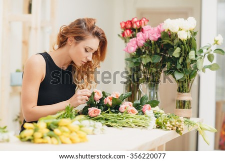 Masterclass of smiling florist at work with bunch of flowers. Florist at work: woman making bouquet of orange roses. Portrait of business woman florist working at flower shop - stock photo