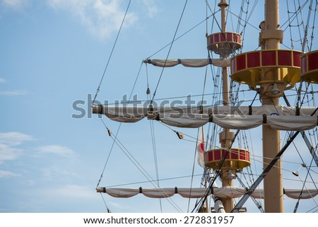 Masts, rigging and the sail of a pirate ship with the blue sky - stock photo