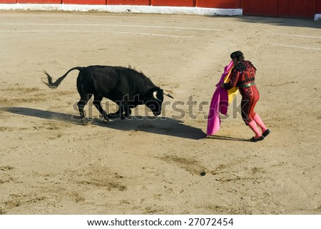 Matador and bull in traditional bullfight (corrida) in Spain - stock photo