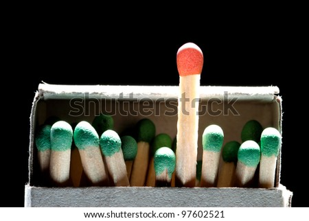 Match boxes and green matches (one match red). A black background. - stock photo