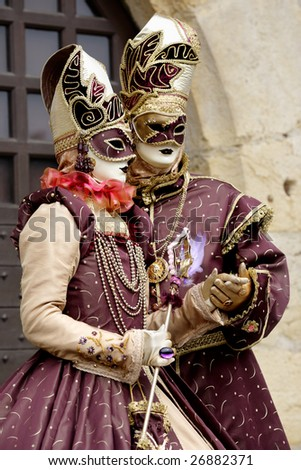 Match costumes for a couple of masks under a medieval scenery (Annecy/France) - stock photo