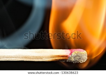 Match with smoke and fire on black - stock photo