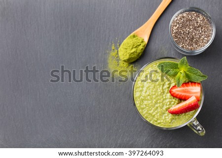Matcha green tea chia seed pudding, dessert with fresh mint and strawberry on a black slate background Healthy breakfast  - stock photo