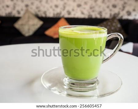 Matcha green tea latte beverage in glass mug. - stock photo