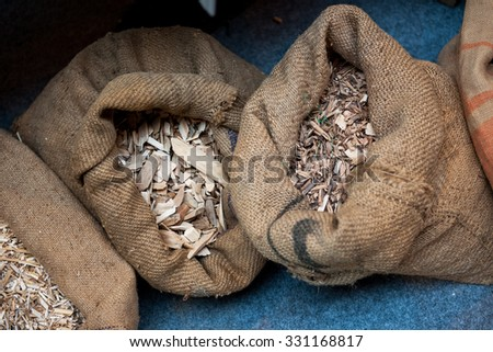 Material used for pellets - compressed organic matter, or biomass made from sawdust in their organic bags next to eachother - stock photo