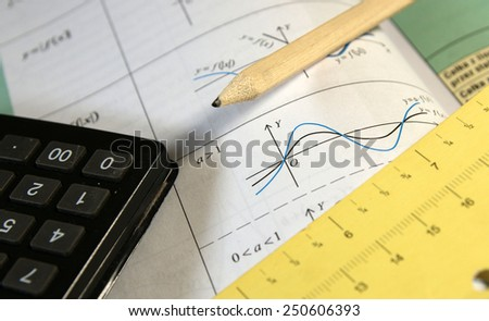 Math study for the exam set  (book, pencil, measure, calculator) - Background shows trigonometry formulas and sinus graphs - stock photo
