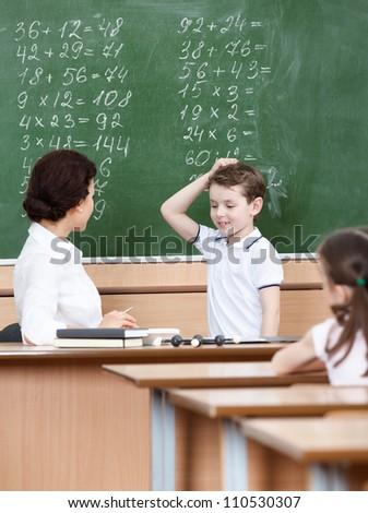 Math teacher questions the pupil who doesn't know the answer - stock photo