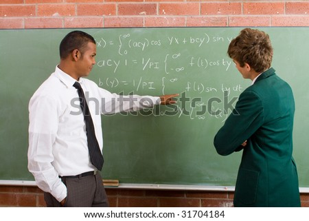 math teacher teaching student in classroom - stock photo