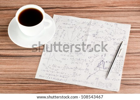 Mathematical calculations on a napkin and cup of coffee - stock photo