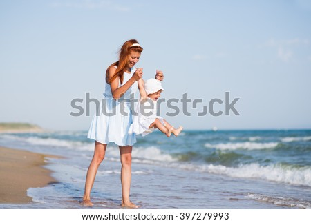 Mather and baby on the sea beach - stock photo