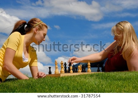 Mather and daughter playing chess - stock photo
