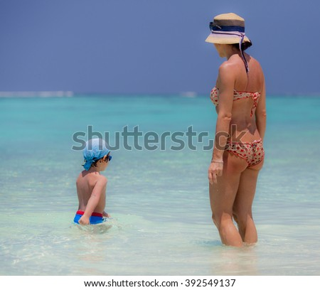 Mather and son on the beach of Maldive Island - stock photo