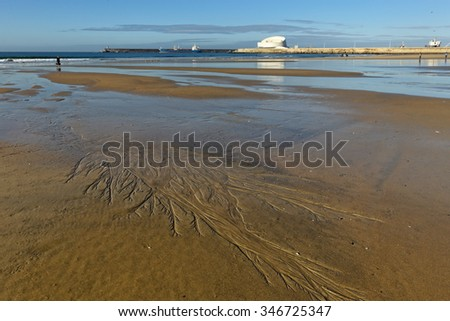 Matosinhos beach at low tide on a bright morning with interesting sand ripples and the south of Leixoes harbor in background seeing the new dashing white passenger terminal. Focus on the foreground. - stock photo