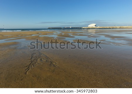 Matosinhos beach at low tide on a bright morning with interesting sand ripples in the foreground and the south of Leixoes harbor in background seeing the new and dashing white passenger terminal.  - stock photo