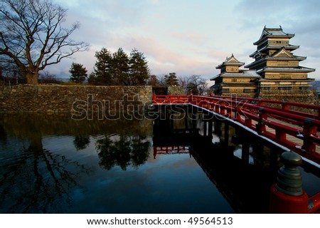 Matsumoto Castle with reflection of red bridge and trees on the water - stock photo