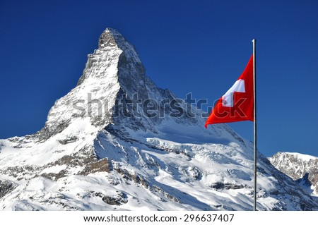 Matterhorn peak in sunny day with red Swiss flag, Switzerland. Matterhorn (peak Cervino) in Swiss Alps with national flag. - stock photo