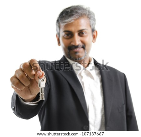 Mature adult Asian Indian man arm out holding a new key over white background - stock photo