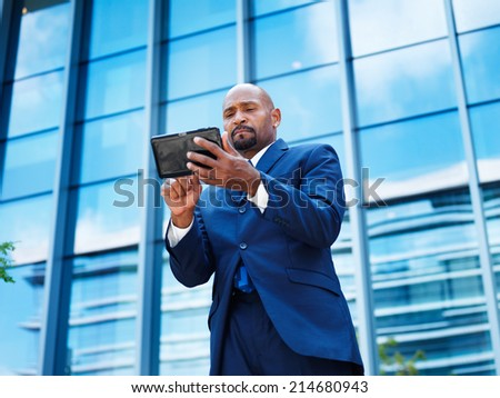 mature African American businessman using tablet in front of office building - stock photo