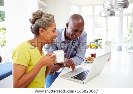 Mature African American Couple Using Laptop At Breakfast - stock photo