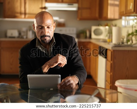 mature african man in kitchen using tablet - stock photo