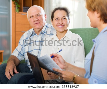 Mature american couple filling questionnaire for employee with laptop of the bank - stock photo