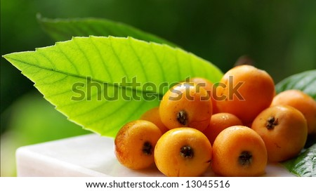Mature and flavorful Loquats with green leaf in deep. - stock photo