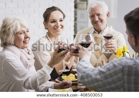 Mature and young married couples toasting, sitting beside table, drinking red wine - stock photo