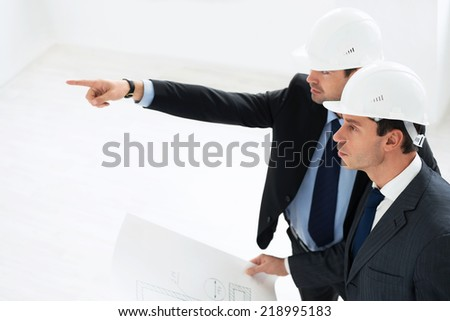 Mature architects in helmets indoor - stock photo