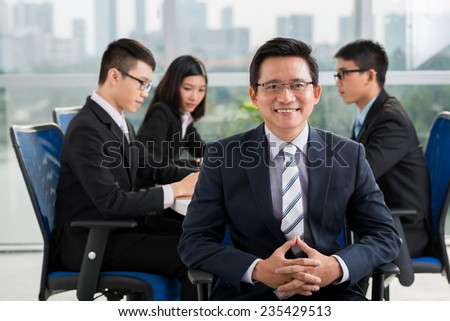 Mature Asian businessman on the background of his young colleagues having meeting - stock photo