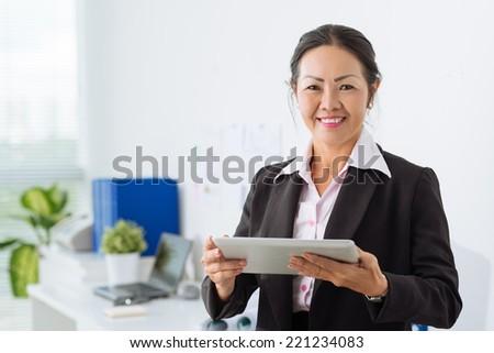 Mature Asian businesswoman holding digital tablet - stock photo