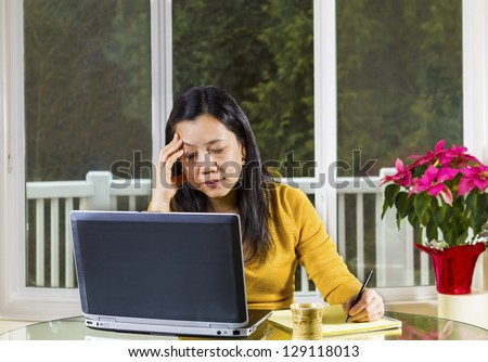 Mature Asian woman working at home, looking stressed, with notebook computer on glass table with large windows in background - stock photo