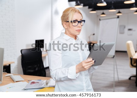 Mature attractive businesswoman standing in office with pc tablet - stock photo
