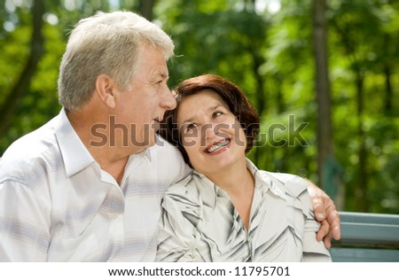 Mature attractive happy couple together in park - stock photo