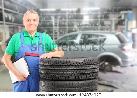 Mature auto mechanic posing on a tires in front of car during automobile maintenance at auto repair shop - stock photo