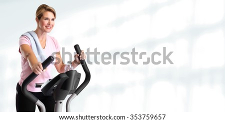 Mature beautiful woman doing exercise on elliptical trainer. - stock photo