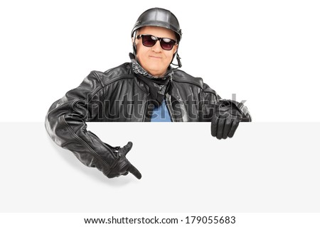 Mature biker pointing on a blank panel isolated on white background - stock photo