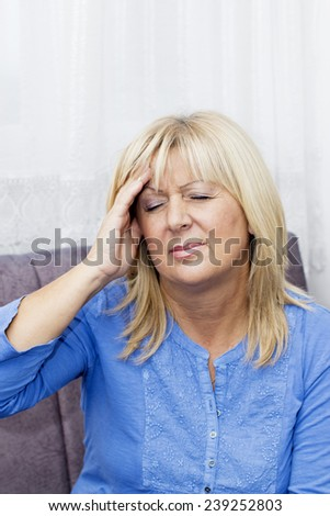 Mature blond haired woman with eyes closed sitting on the sofa  and touching her  head in pain. - stock photo