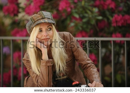 Mature blond woman with bike outdoors in spring smiling - stock photo