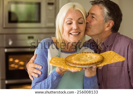 Mature blonde holding fresh pie with husband kissing her at home in the kitchen - stock photo