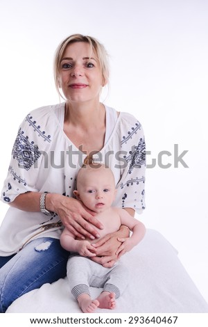 mature blonde woman holding and taking care of her lovely new born baby boy  - stock photo